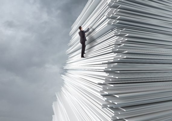 man climbing a big pile of papers